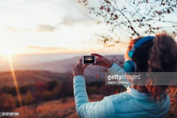 Woman taking photo of the sunset