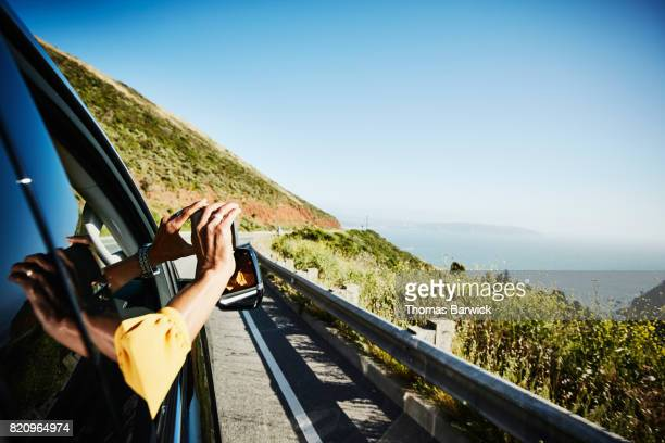 Woman taking photo of vista out of car window with smartphone