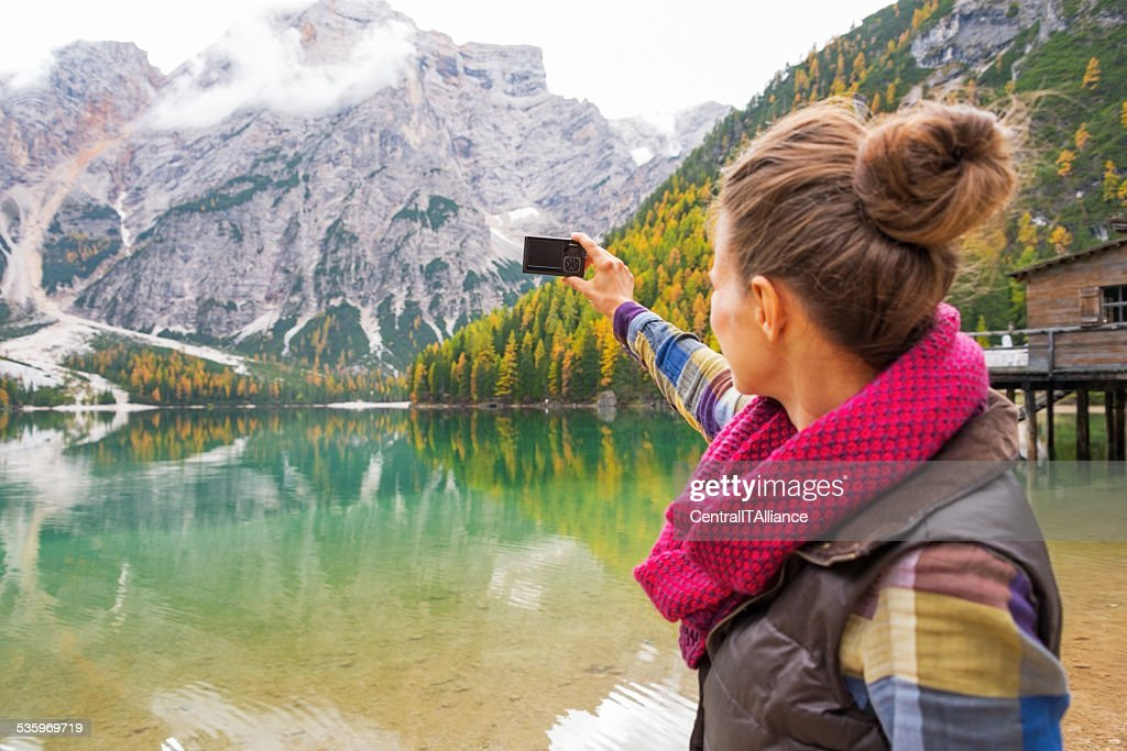 Woman taking photo on lake braies in south tyrol, italy : Stock Photo