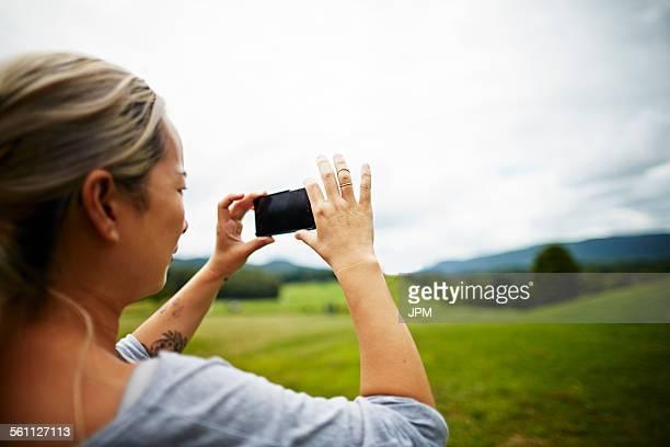 Woman taking photo on smartphone of rural field landscape