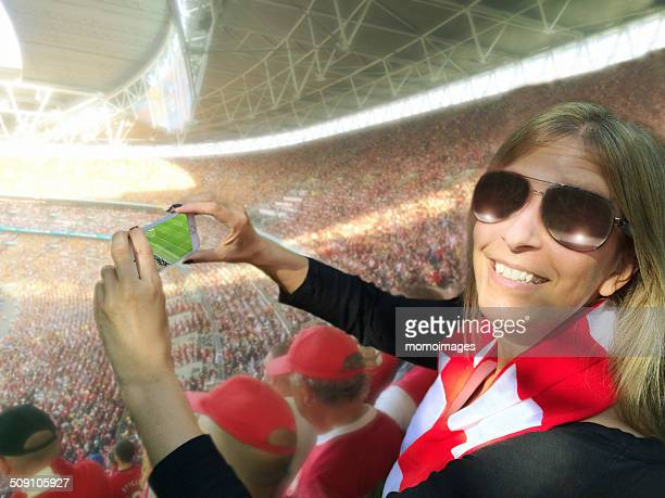 Woman taking photo with phone at football match