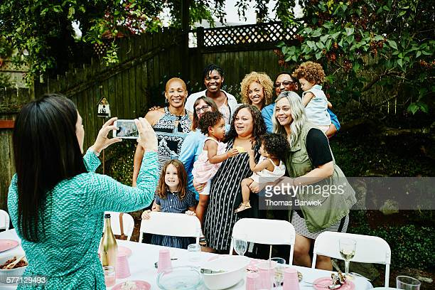 Woman taking photo with smartphone of family