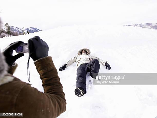 Woman taking photograph of man lying in snow