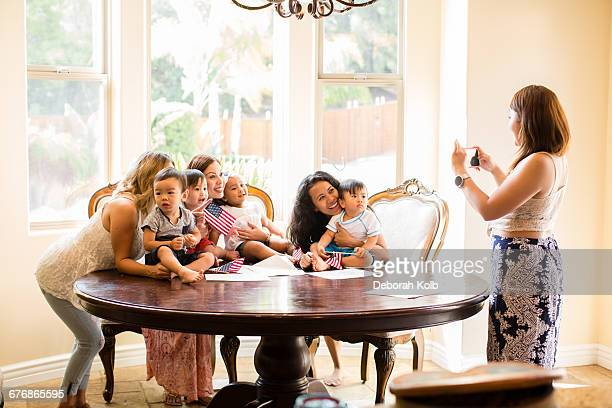 Woman taking photograph of mothers and babies at dining table