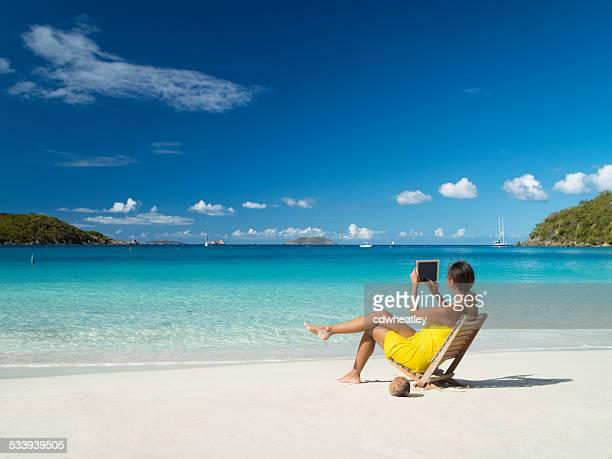 Femme prenant des photographies avec het une tablette au bord de la plage