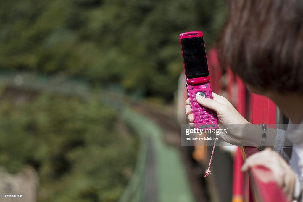 Woman taking photos from train : Stock Photo