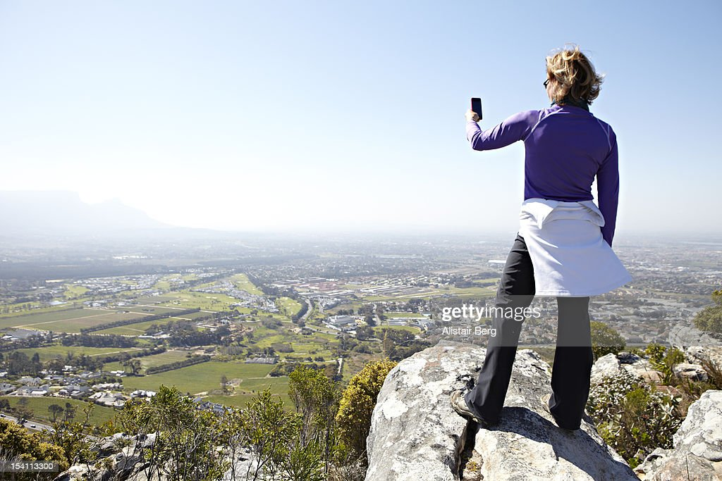 Woman taking picture from top of hill : Stock Photo