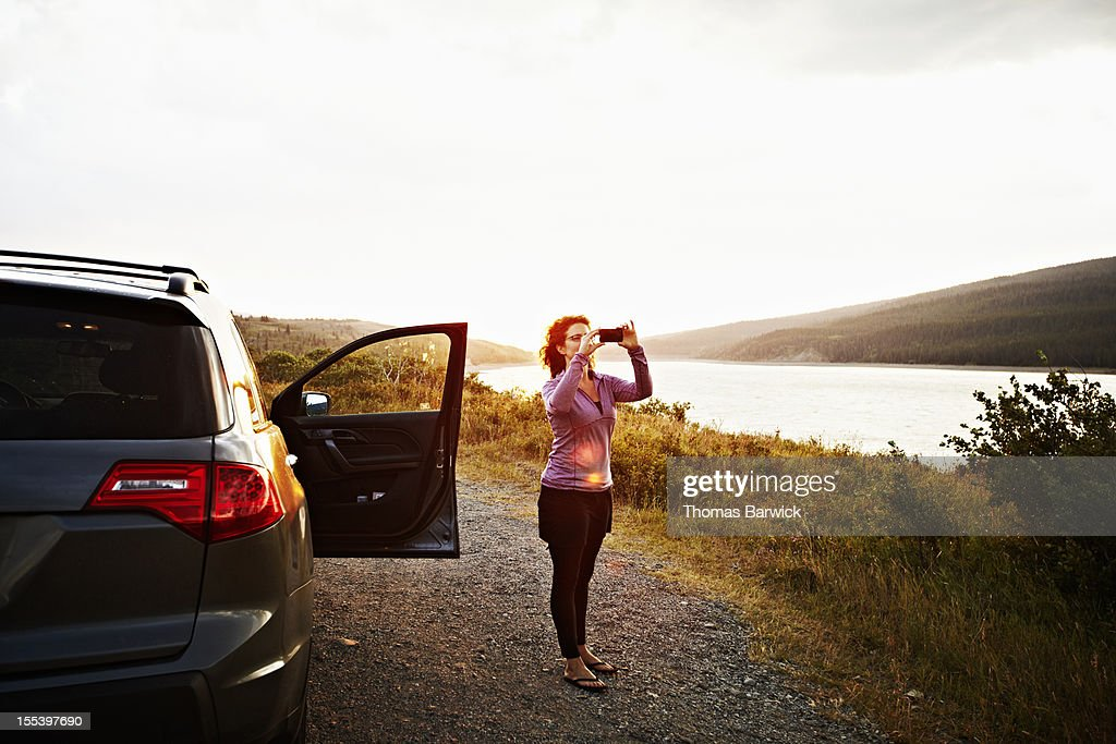 Woman taking picture in Glacier National Park : Stock Photo
