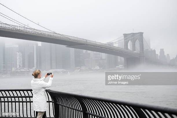 Woman taking picture of bridge