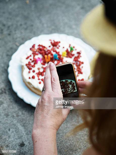 Woman taking picture of cake with her cell phone