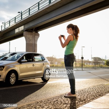 Woman taking picture of her car. : Stock Photo