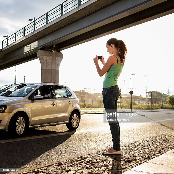 Woman taking picture of her car.