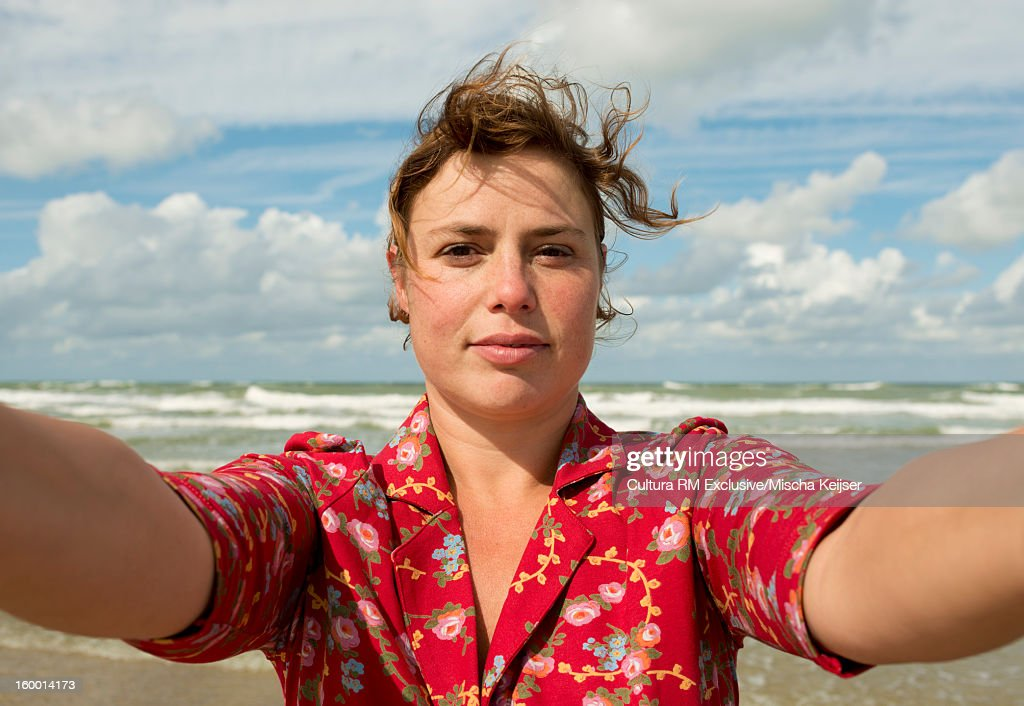 Woman taking picture of herself on beach