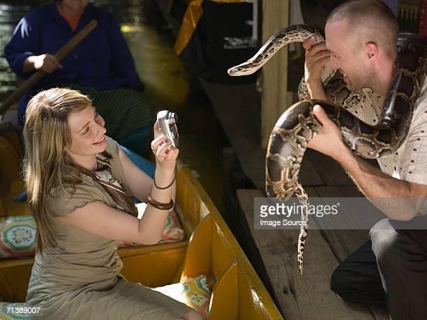 Frau nimmt Foto von Mann hält snake