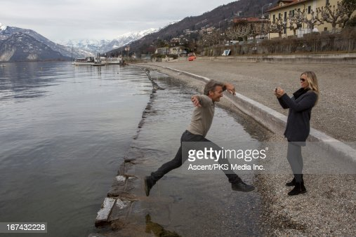 Woman taking picture of man in mid-air jump : Foto de stock