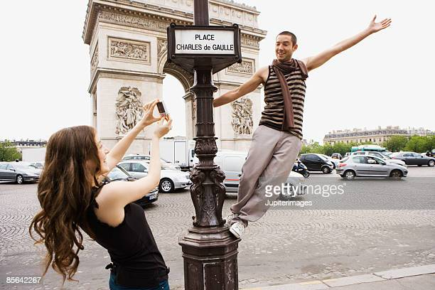 Woman taking picture of man standing on street sign in front of Arc de Triomphe,  Paris,  France