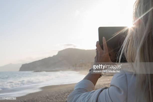 Woman taking picture of surf crashing