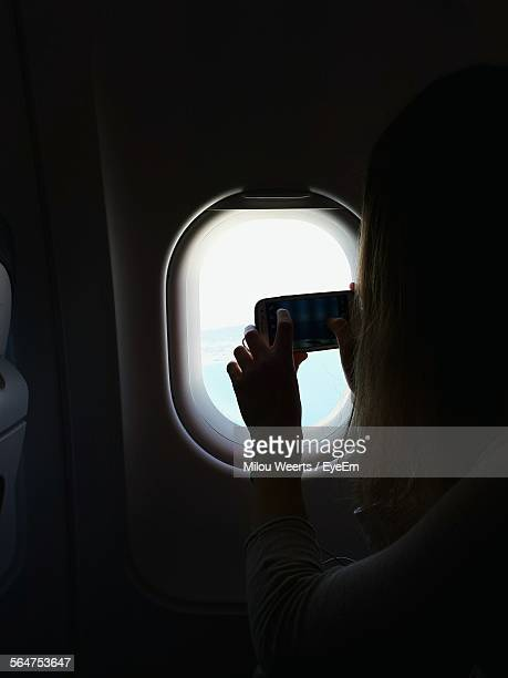 Woman Taking Picture On Airplane