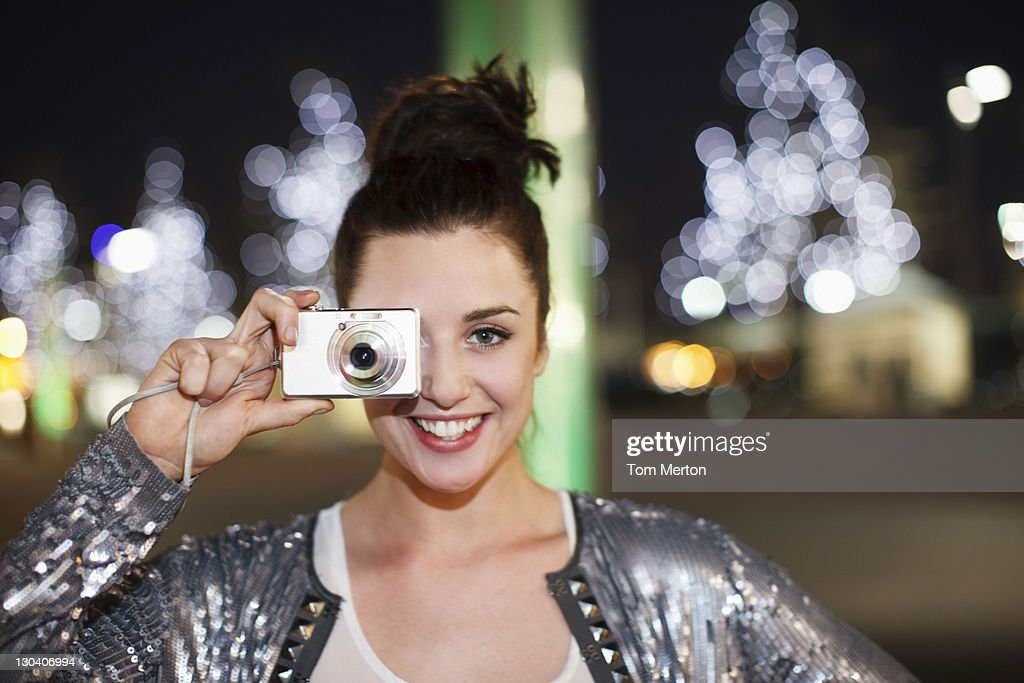 Woman taking picture on city street at night : Stock Photo