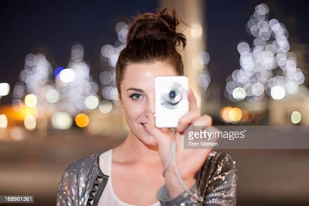 Frau nimmt Foto auf der Straße in der Stadt bei Nacht