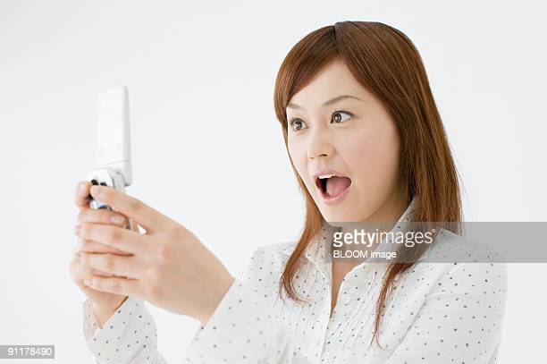 Woman taking picture with mobile phone, studio shot