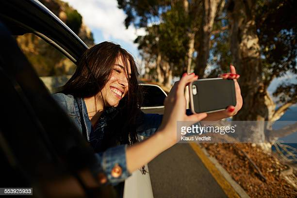 Woman taking picture with phone out of car window