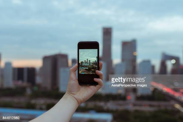 Woman taking pictures from personal point of view with smartphone of the Beijing Skyline