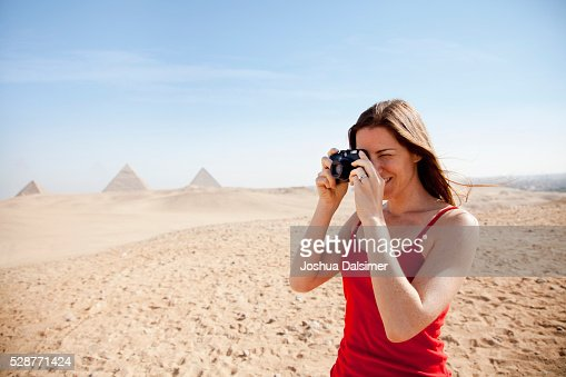 Woman taking pictures in the desert : Stock Photo