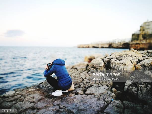 Woman Taking Pictures On Shore