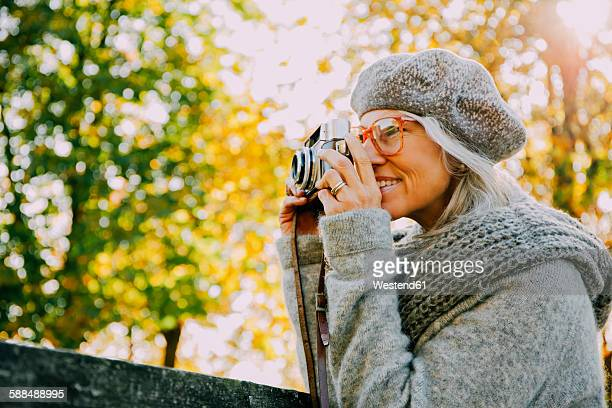 Woman taking pictures with an old camera in an autumnal park