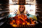 Woman Taking Roast Turkey Out Of The Oven. Smiling