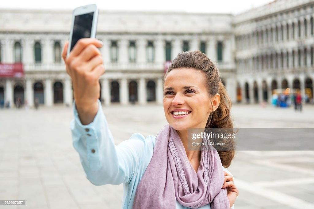 Woman taking self photo with cell phone in venice, italy : Stock Photo
