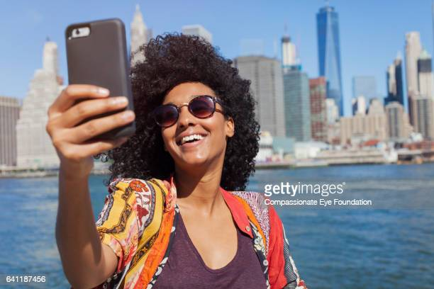 Woman taking self portrait with Manhattan skyline