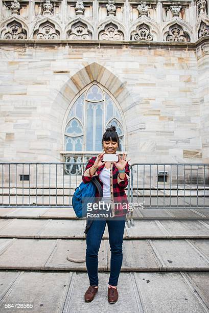 Woman taking selfie in front of Duomo Cathedral, Milan, Italy