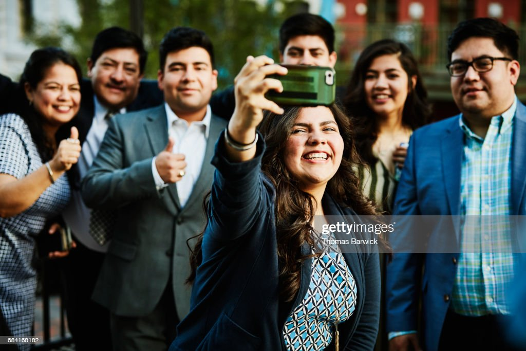 Woman taking selfie on smartphone with family on restaurant deck : Stock Photo