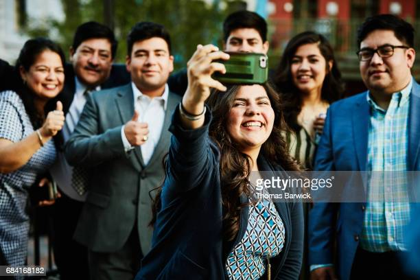 Woman taking selfie on smartphone with family on restaurant deck