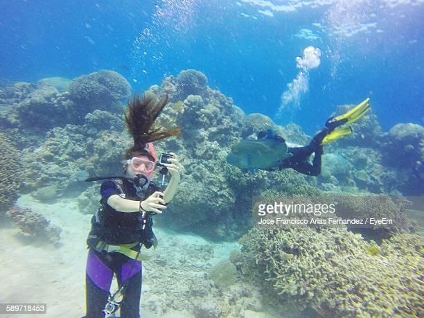 Woman Taking Selfie While Scuba Diving In Sea
