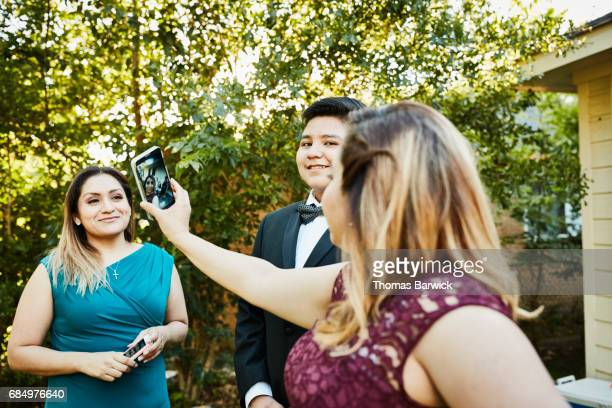 Woman taking selfie with family members in backyard before quinceanera