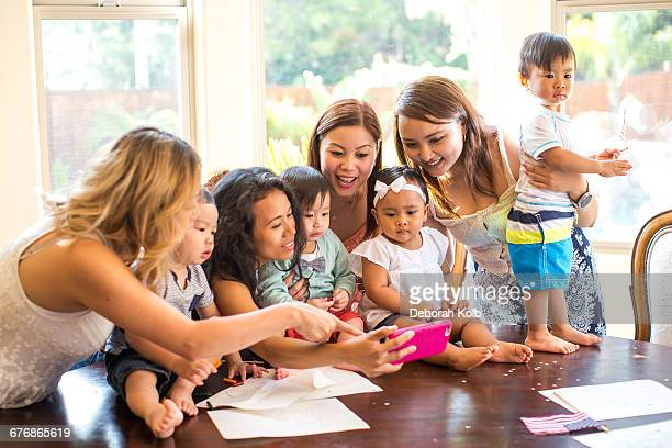 Woman taking selfie with mothers and babies at dining table