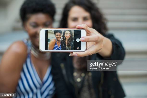 Woman taking selfie with young female friend from mobile phone