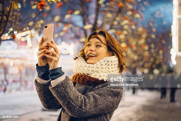 Woman taking selfies on the Christmas decorated street