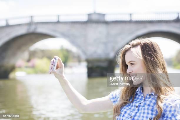 Retrato de una mujer tomando estacionamiento sin servicio de valet junto al río