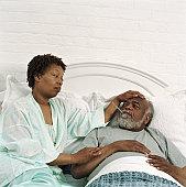 Woman taking senior man's temperature in bed