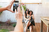 Woman taking smartphone photograph of female friends