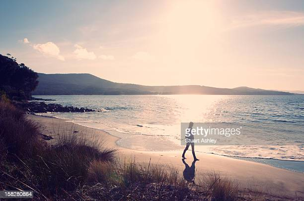 Woman taking sunset walk on beach