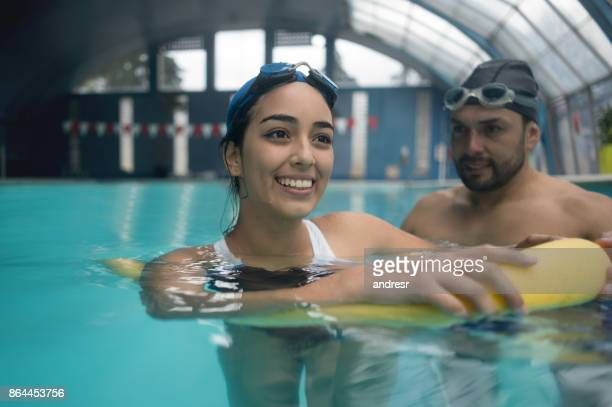 Woman taking swimming lessons in an indoor pool