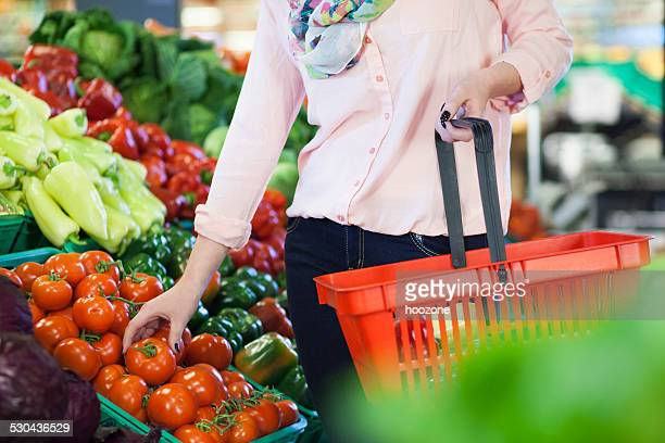 Femme prenant la tomate