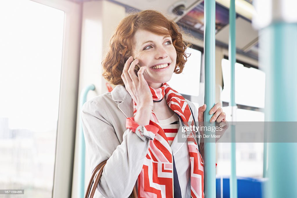 Woman taling on  phone, while on public transport : Stock Photo