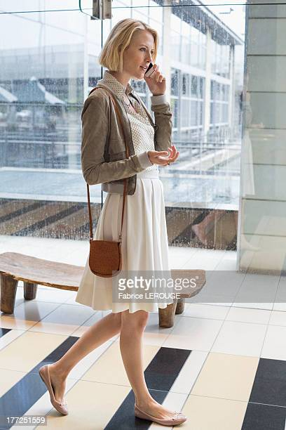 Woman talking on a mobile phone while walking on an airport