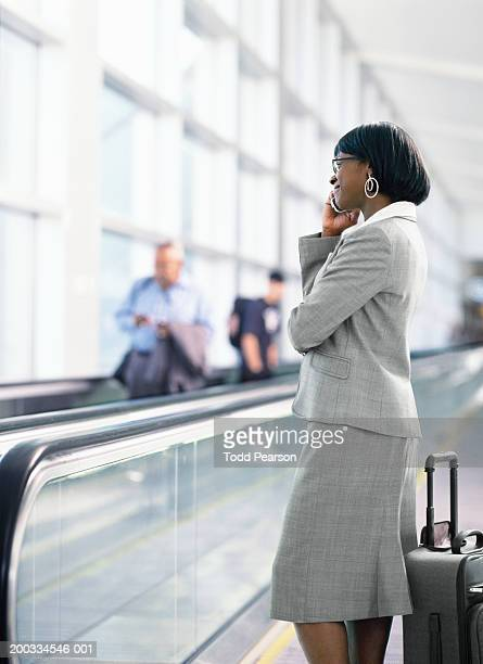 Woman talking on cell phone beside moving walkway in airport